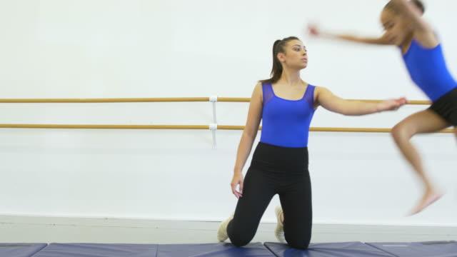 gymnastics coach helps girl do aerial cartwheel - 8 9 years stock videos & royalty-free footage