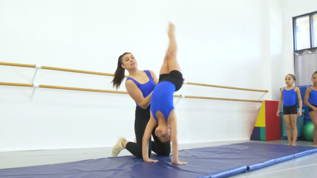 gymnastics coach helps girl do back handspring - 8 9 years stock videos & royalty-free footage