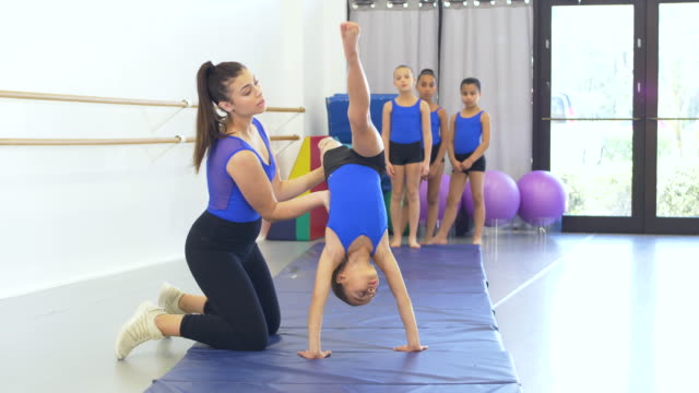 gymnastics coach with girls doing back walkovers - 8 9 years stock videos & royalty-free footage
