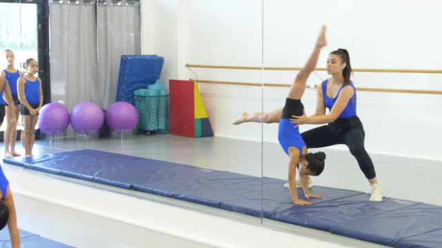 gymnastics coach with girls doing front walkovers - 8 9 years stock videos & royalty-free footage