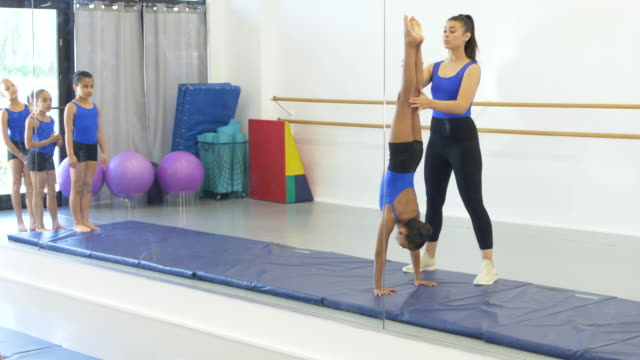 gymnastics coach with girls doing handstands - 8 9 years stock videos & royalty-free footage