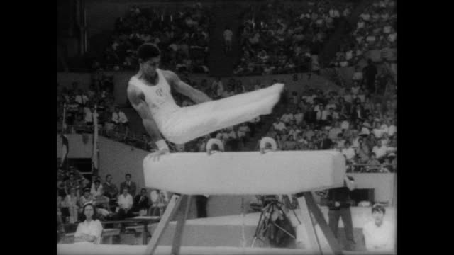 gymnasts perform at pan american games in winnipeg canada / men perform on horse as indoor crowd applauds / mark cohn of philadelphia stands on 1st... - 1967 stock videos & royalty-free footage