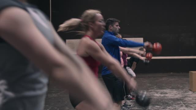 vídeos de stock, filmes e b-roll de gymters swinging kettlebells in a gym box - aperfeiçoamento pessoal