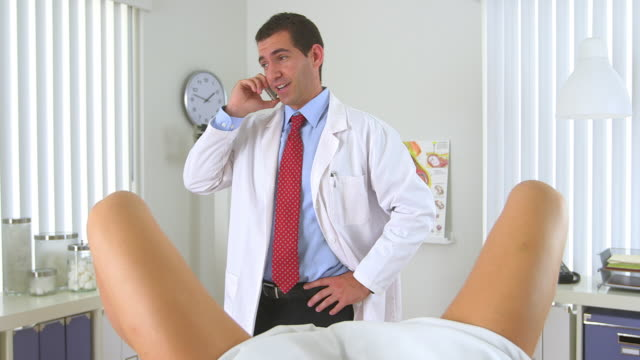 gynecologist talking on his smartphone - gynecological examination stock videos and b-roll footage