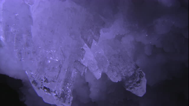 a gypsum crystal rock formation hangs like a chandelier from a lechuguilla cave ceiling. available in hd. - rock crystal stock videos and b-roll footage