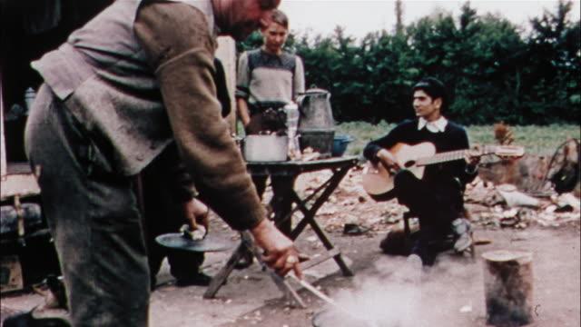 vidéos et rushes de a gypsy family performs chores in front of a trailer. - minorité
