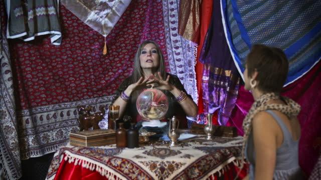 vídeos de stock e filmes b-roll de cigano cartomante com jovem - paranormal