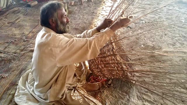 gypsy man weaving baskets with tree branches for his earnings - intrecciare cestini video stock e b–roll