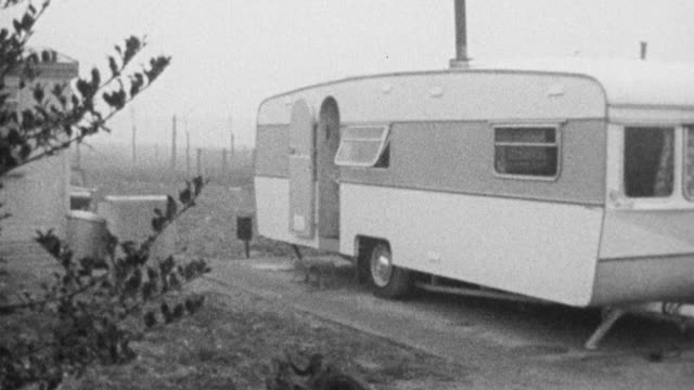 vidéos et rushes de 1972 montage gypsy trailers parked in front of house, and girls walking out of trailer and into house nearby / bushey, england, united kingdom - minorité