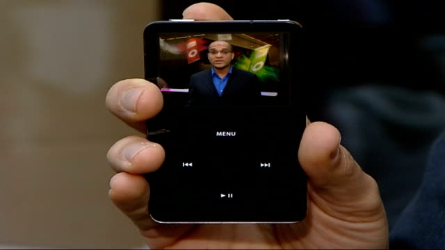 hacker claims to have broken apple's i-tunes digital lock; england: london: ext reporter to camera on ipod screen as held by reporter pull out... - mp3 player stock videos & royalty-free footage
