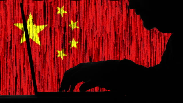hacker hacking typing code on his laptop with chinese flag  in background - chinese culture stock videos & royalty-free footage