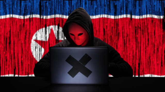 hacker hacking typing code on his laptop with north korea flag and binary code animation overlay in background - tragedy mask stock videos & royalty-free footage