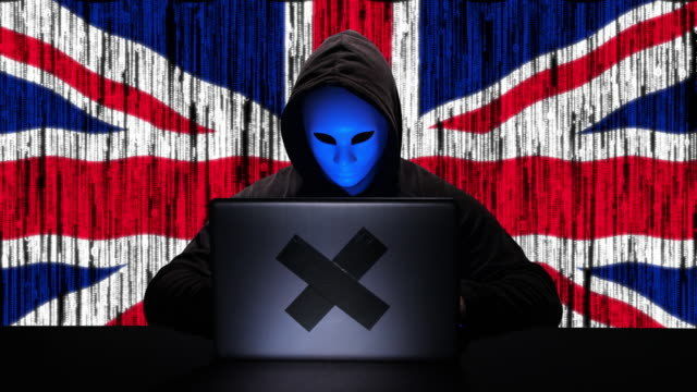 hacker hacking typing code on his laptop with uk united kingdom flag and binary code animation overlay in background - tragedy mask stock videos & royalty-free footage