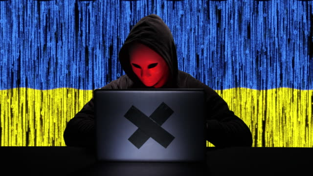 hacker hacking typing code on his laptop with ukraine flag and binary code animation overlay in background - tragedy mask stock videos & royalty-free footage