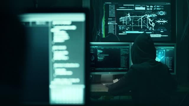 vídeos y material grabado en eventos de stock de hacker en carcasa resquebrajamiento código usando ordenador portátil y los ordenadores de su oscuro hacker habitación - red artículos deportivos
