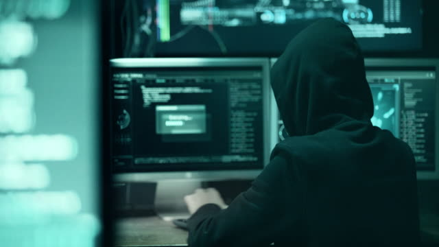 stockvideo's en b-roll-footage met hacker in kap kraken code met laptop en computers vanuit zijn kamer donker hacker - terrorisme
