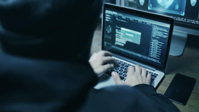 hacker in hood cracking code using laptop and computers from his dark hacker room - hacker stock videos and b-roll footage