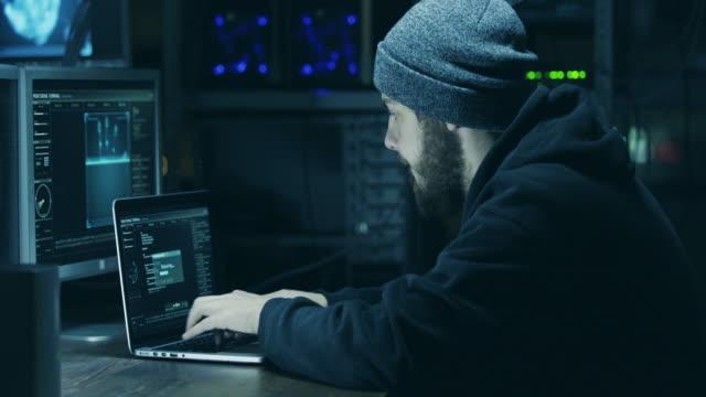vidéos et rushes de hacker dans la capuche préparation du code promotionnel en utilisant un ordinateur portable et des ordinateurs - masque de protection