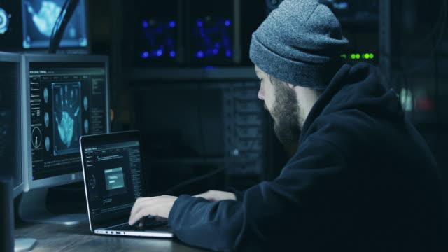 hacker in kapuze knacken code mit laptop und computer - spion stock-videos und b-roll-filmmaterial