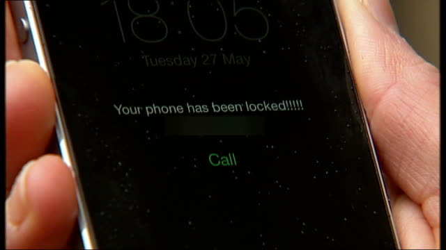 hacker locks iphones and ipads and demands a ransom to unlock devices; england: london: ext woman taking iphone mobile phone from pocket message on... - aprire una serratura video stock e b–roll