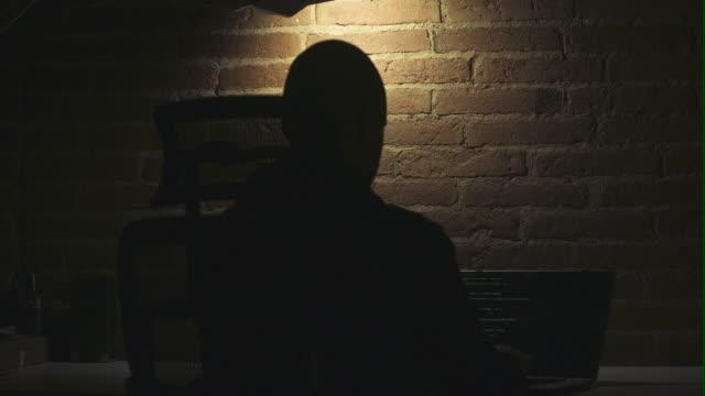 vidéos et rushes de hacker man typing code at laptop - se cacher
