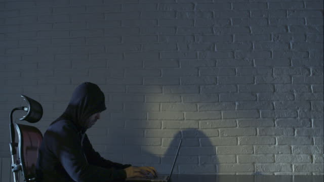 Hacker man with iconic hood clothing typing code at laptop