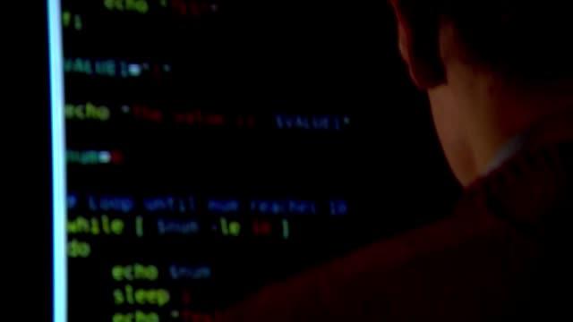 stockvideo's en b-roll-footage met hacker sitting at computer - computermisdaad