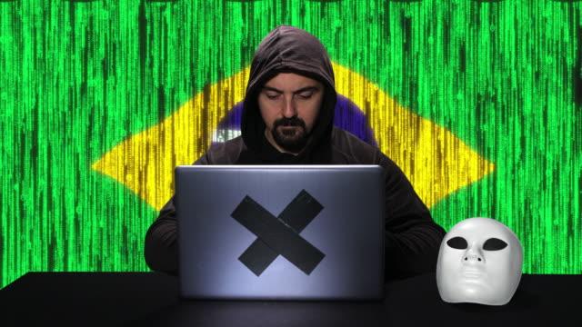 vídeos de stock, filmes e b-roll de hacker que datilografa o código que corta em seu portátil com bandeira de brasil com sobreposição da animação do código no fundo - deep web