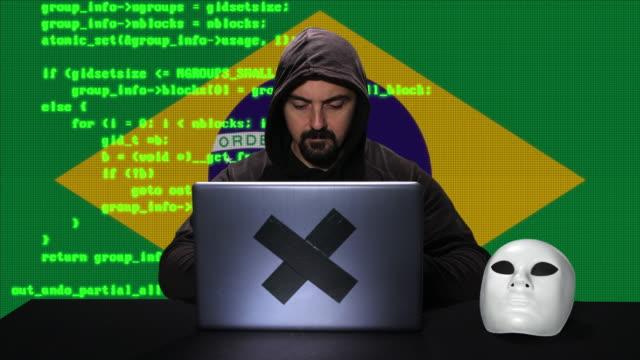 vídeos de stock, filmes e b-roll de hacker que datilografa o código que corta em seu portátil com bandeira de brasil com sobreposição da animação do código no fundo - vírus de computador