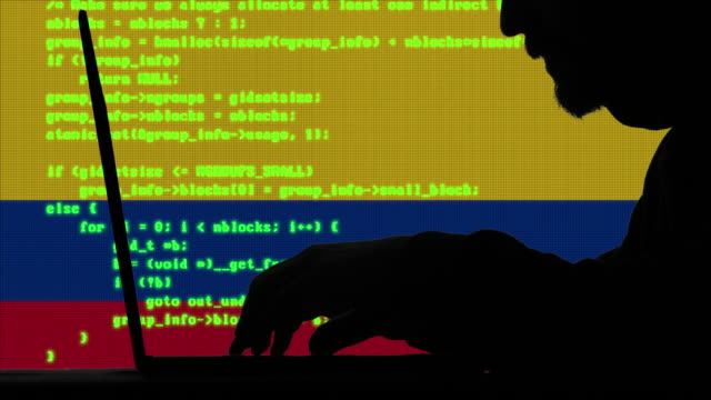 hacker typing code on his laptop with colombian flag in background - colombian flag stock videos and b-roll footage