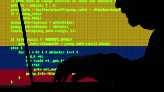 ハッカーは、バックグラウンドでコロンビアの旗を持つ彼のラップトップ上のコードを入力します - アノニマス点の映像素材/bロール