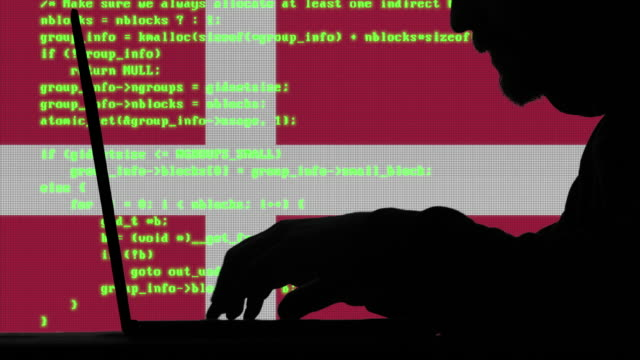 hacker typing code on his laptop with danish flag in background - danish flag stock videos and b-roll footage