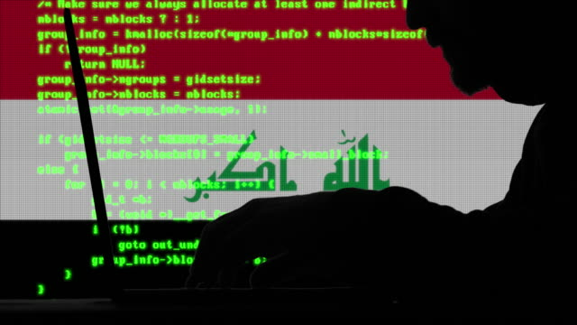 hacker typing code on his laptop with iraqi flag in background - iraqi flag stock videos and b-roll footage