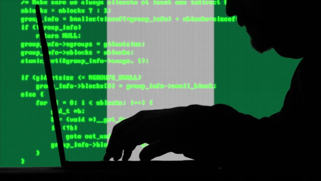 hacker typing code on his laptop with nigerian flag in background - nigerian flag stock videos & royalty-free footage