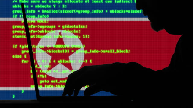 hacker typing code on his laptop with north korean flag in background - computer crime stock videos & royalty-free footage