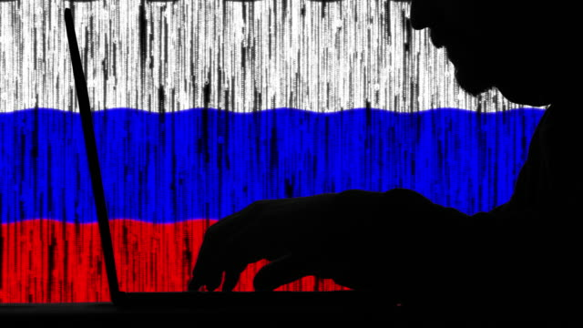 hacker typing code on his laptop with russian flag in background - computer hacker stock videos & royalty-free footage