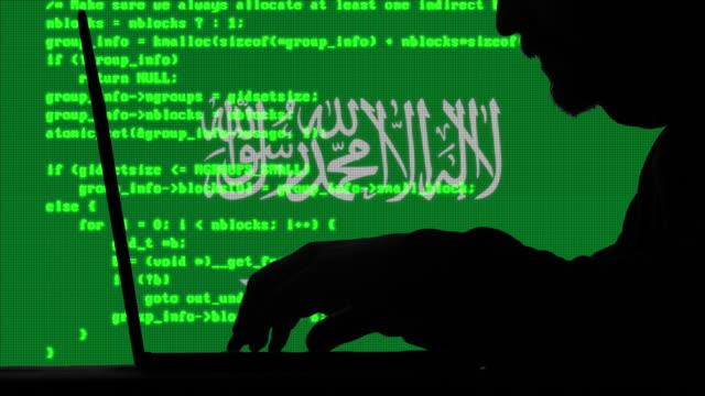 ハッカーは、背景にサウジアラビアの旗を持つ彼のラップトップ上のコードを入力します - アノニマス点の映像素材/bロール