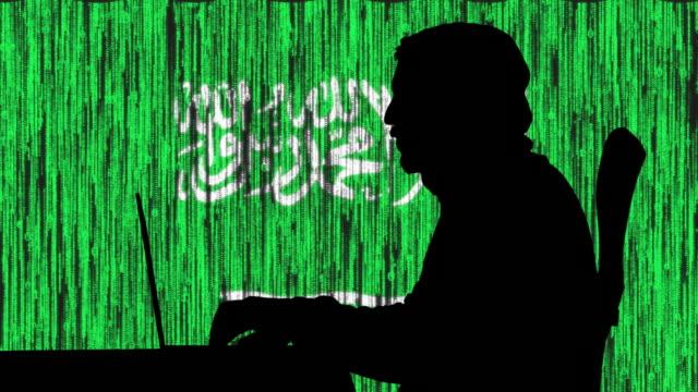 vídeos de stock e filmes b-roll de hacker typing code on his laptop with saudi arabian flag in background - arábia saudita
