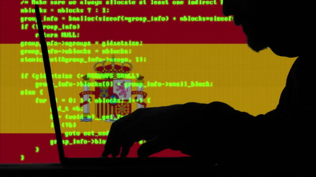 hacker typing code on his laptop with spanish flag in background - spanish flag stock videos and b-roll footage