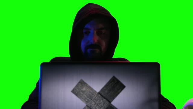 vídeos de stock, filmes e b-roll de hacker com a capa que olha a câmera e apontar o dedo, fundo verde da tela da chave do chroma - segurança de rede