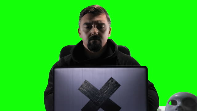 hacker with hood typing code on his laptop, chroma key green screen background - corporate theft stock videos and b-roll footage