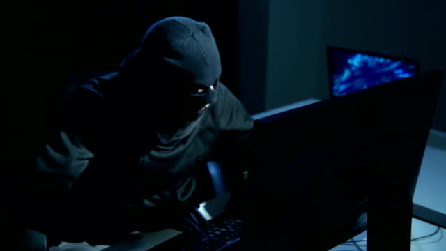 Hacker with mask cracking code