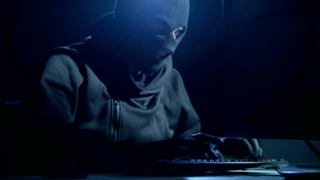 hacker with mask cracking code - conspiracy stock videos and b-roll footage