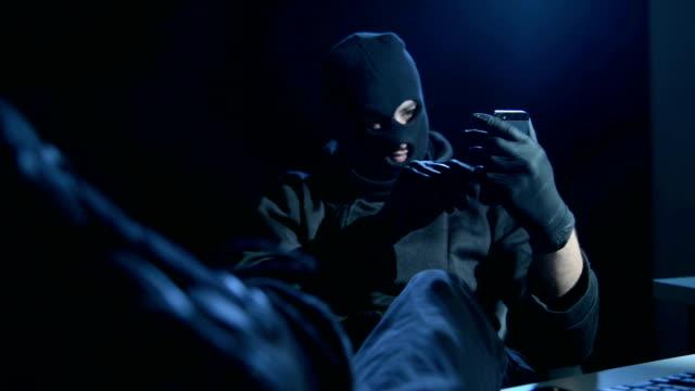 vídeos de stock, filmes e b-roll de hacker com smartphone - burglar
