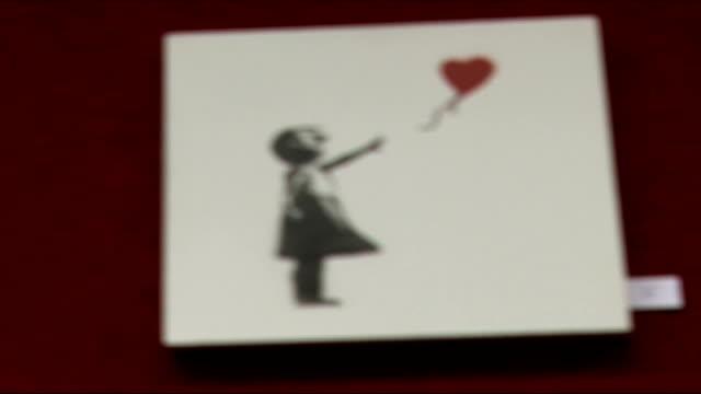 vídeos de stock, filmes e b-roll de hackney council to remove street art by graffiti artist banksy int 'balloon girl' painting on display spray painting of monkey wearing sign reading... - pintor artista