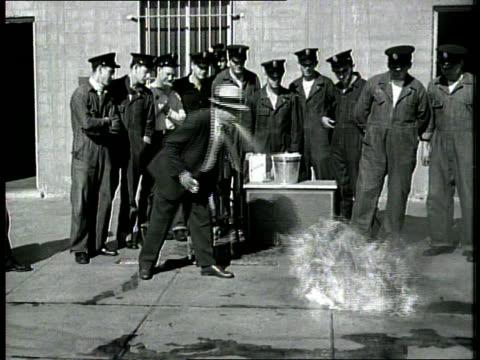 vidéos et rushes de hadji ali the human camel / he spits kerosene and water onto a fire / laughs as he spits water at the camera lens - kérosène