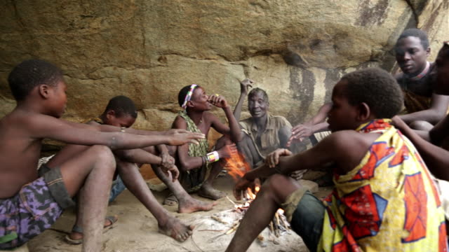 hadzabe men and boys sitting by the fire and talking in rocks shade