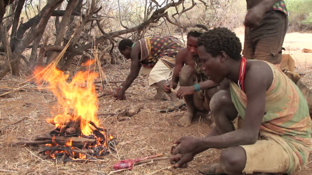 hadzabe men eating by the fire 1