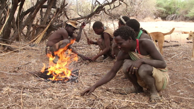 hadzabe men eating by the fire 4 - crouching stock videos & royalty-free footage