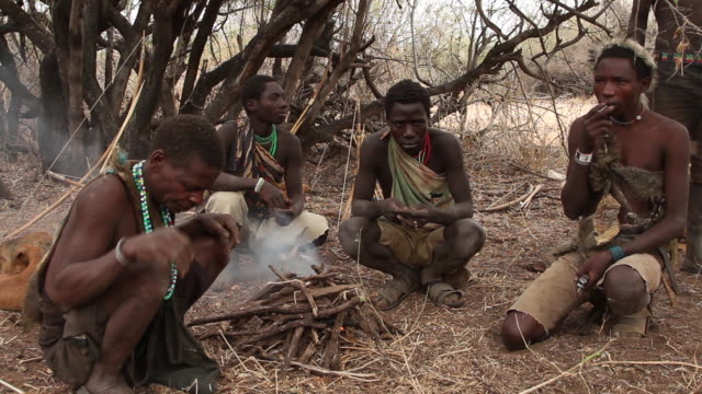 hadzabe men sitting and smoking by the fire